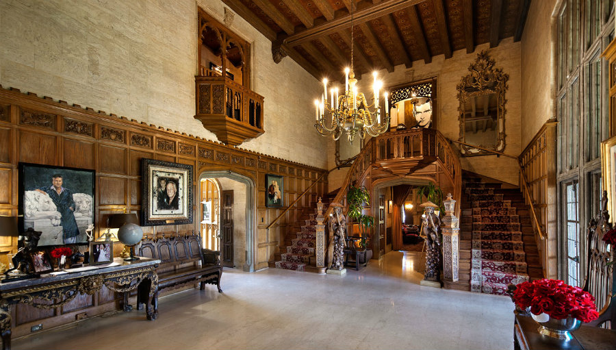 Playboy Mansion's main entrance features an old-school style with pictures of Hugh Hefner on the wall. Image Source: Robb Report