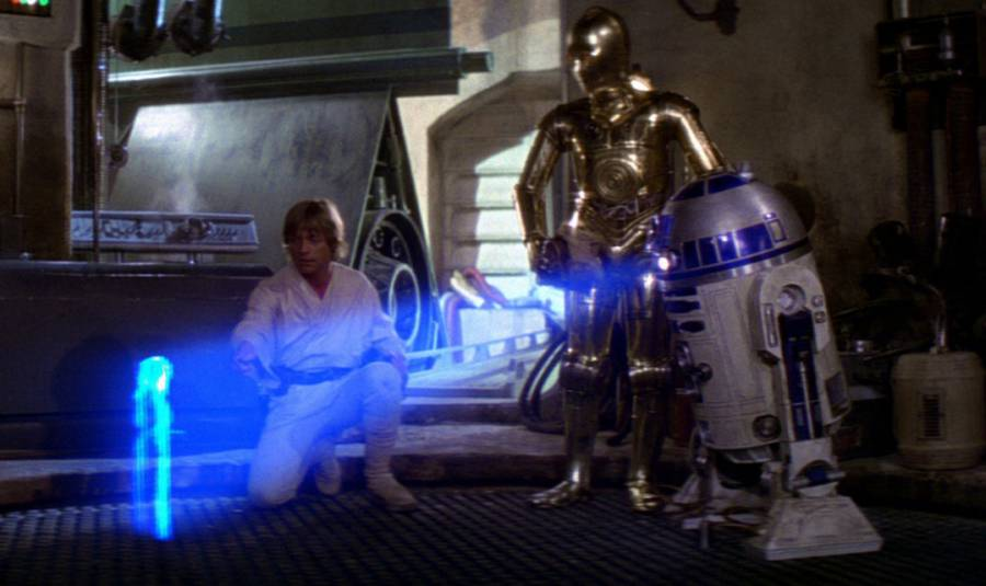 Luke-Skywalker-and-C-3PO-watch-R2-D2-display-a-hologram-of-Princess-Leia-in-Star-Wars-A-New-Hope