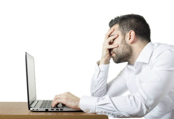 Frustrated man in front of a laptop.